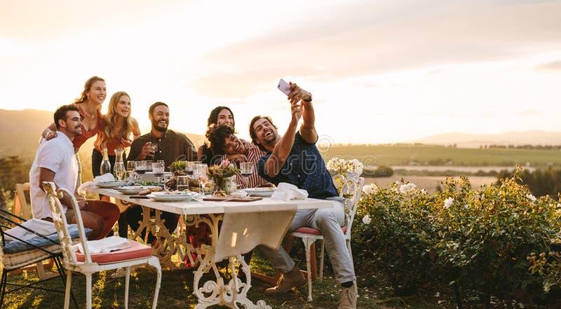 采取selfie的小组朋友在晚餐会 库存图片