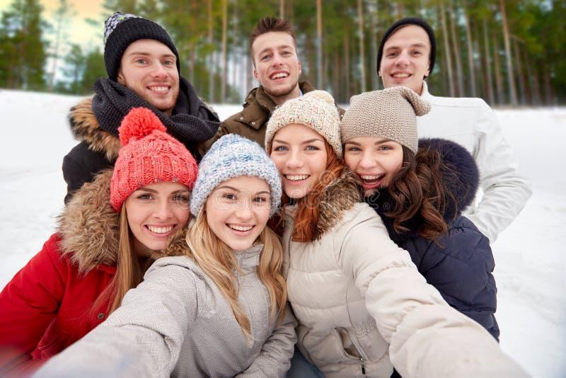 采取selfie的小组朋友户外在冬天 免版税库存照片