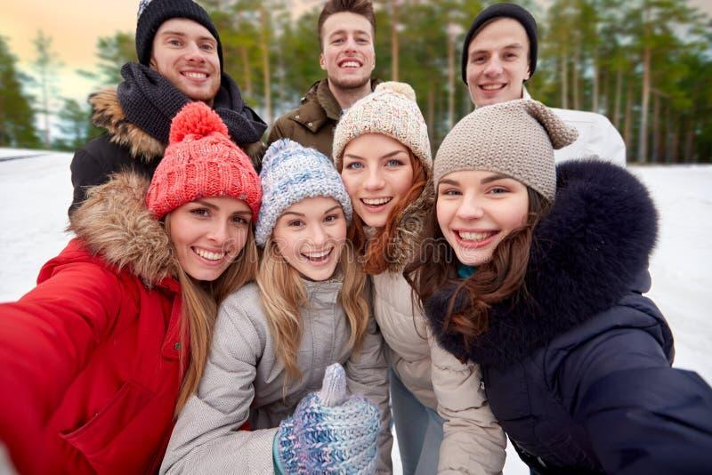 采取selfie的小组朋友户外在冬天 免版税库存图片