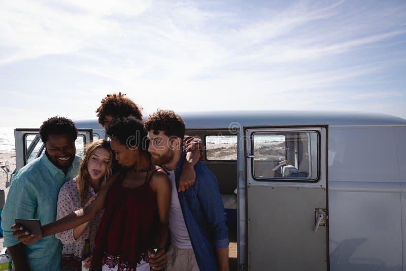 采取selfie的小组朋友,当饮用啤酒在海滩时 免版税库存照片