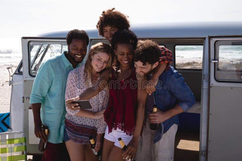 采取selfie的小组朋友,当饮用啤酒在海滩时 免版税库存图片