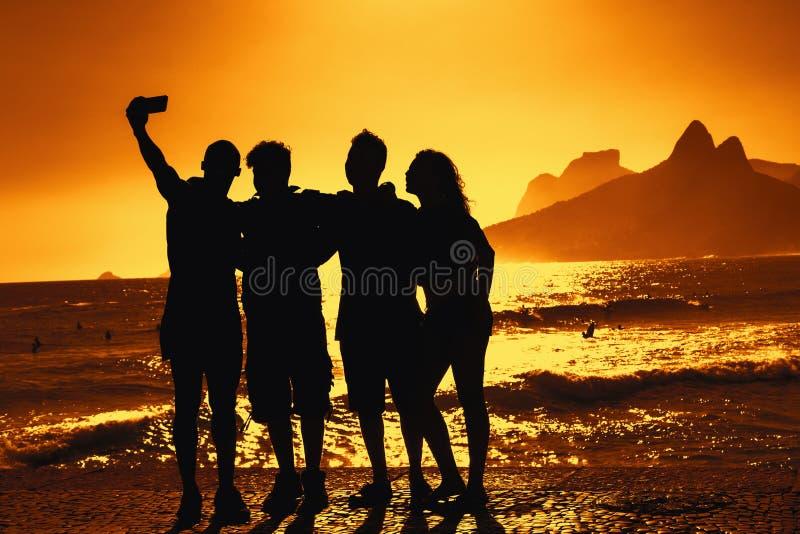 采取selfie的小组游人在海滩在里约热内卢 库存照片