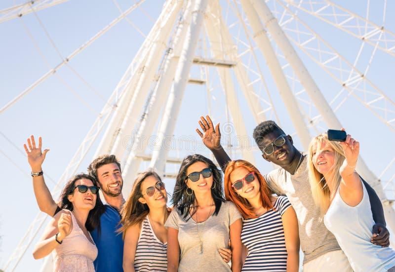 采取selfie的小组多种族愉快的朋友在弗累斯大转轮 免版税库存照片