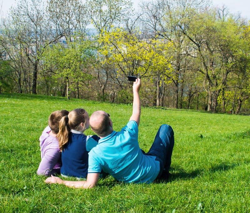 采取selfie的小组微笑的朋友在公园 免版税库存照片