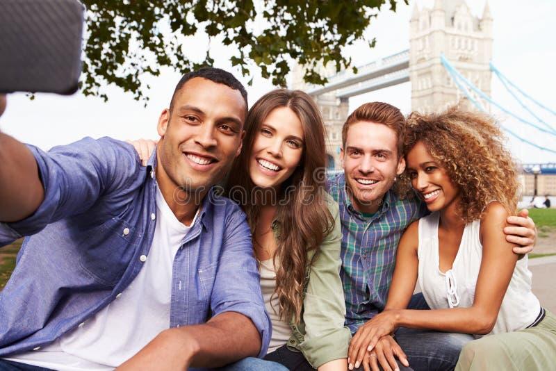 采取Selfie的小组朋友由塔桥梁在伦敦 免版税图库摄影