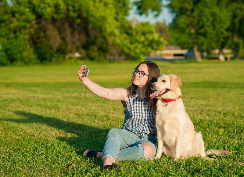 采取selfie的少妇和她友好的狗在公园 免版税库存照片