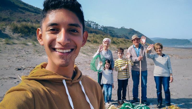 采取selfie的年轻人对小组志愿者在清洗海滩以后 库存图片