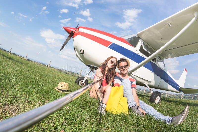 采取selfie的年轻夫妇在私有飞机旅行旅行 免版税库存图片