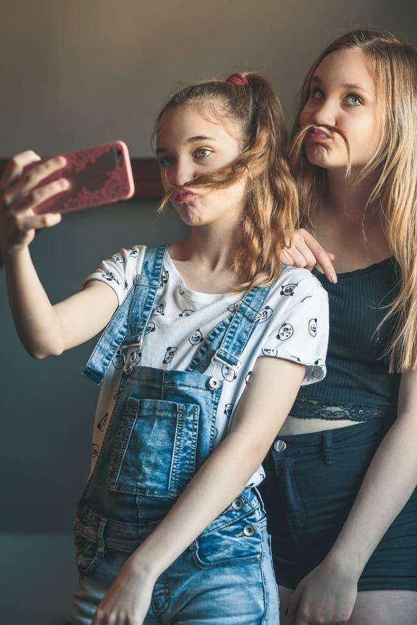 采取selfie的年轻女人,使用智能手机照相机 免版税图库摄影