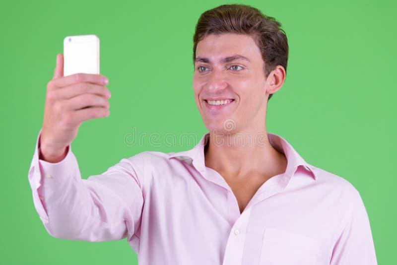 采取selfie的年轻愉快的商人的面孔 免版税库存照片