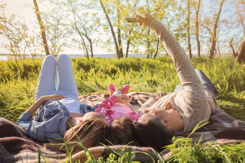 采取selfie的幸福家庭,当说谎在绿草在公园时 免版税库存图片