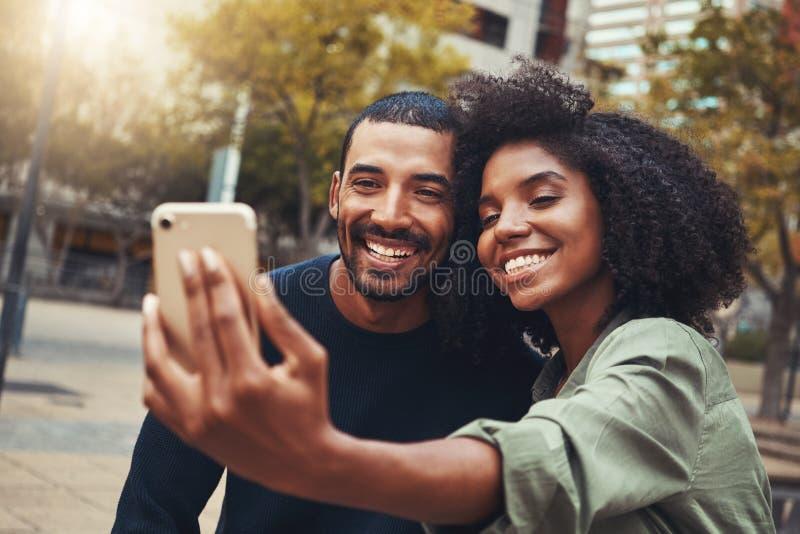 采取selfie的微笑的年轻夫妇在城市公园 免版税库存照片