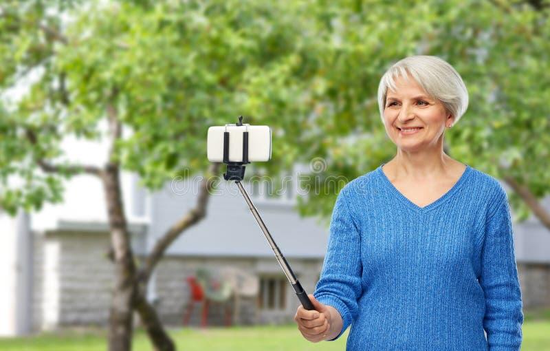 采取selfie的微笑的资深妇女由智能手机 免版税库存图片