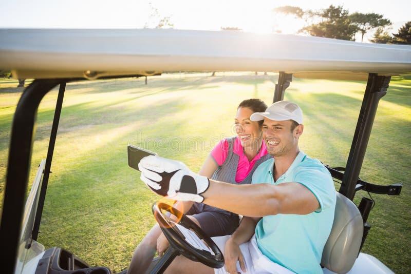 采取selfie的微笑的高尔夫球运动员夫妇 免版税库存图片
