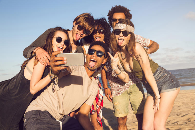 采取selfie的快乐的不同种族的朋友在海滩在晴天 免版税库存图片