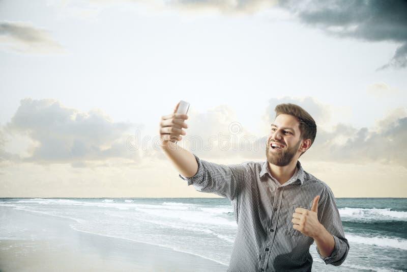 采取selfie的快乐的人在海滩 免版税库存图片