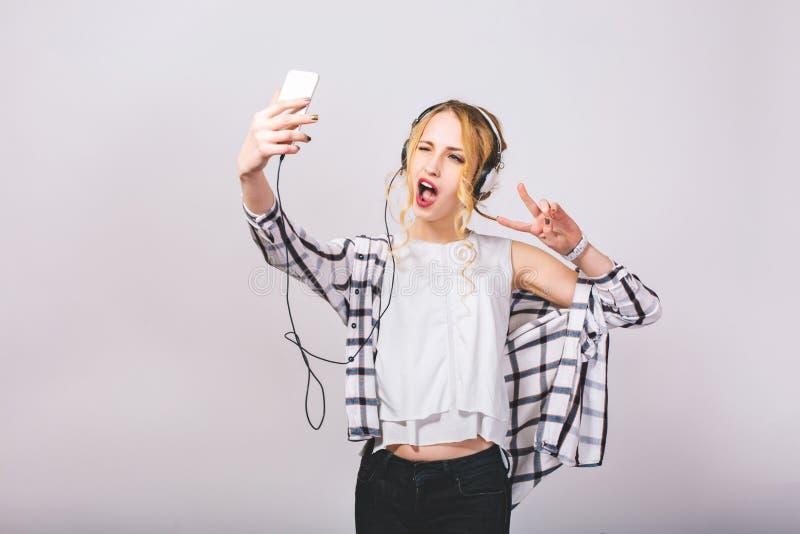 采取selfie的快乐的可爱的年轻女人,做鬼脸,显示手指和平唱歌 获得快乐的白肤金发的女孩乐趣 免版税库存照片