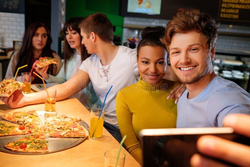 采取selfie的快乐的多种族朋友在比萨店 库存照片