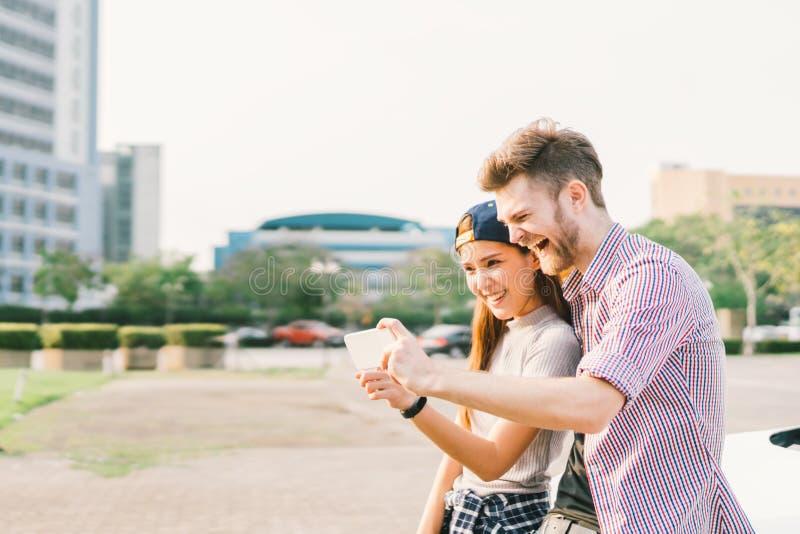 采取selfie的愉快的不同种族的夫妇在日落期间在城市,乐趣和微笑,爱或者小配件技术概念 图库摄影