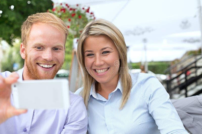 采取selfie的愉快的企业夫妇在室外餐馆 免版税图库摄影