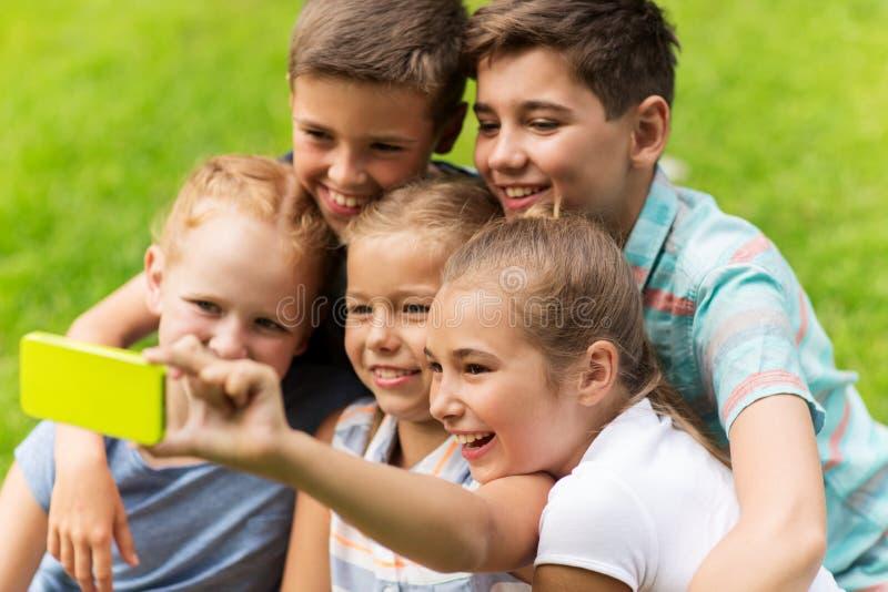 采取selfie的愉快的孩子或朋友在夏天公园 图库摄影