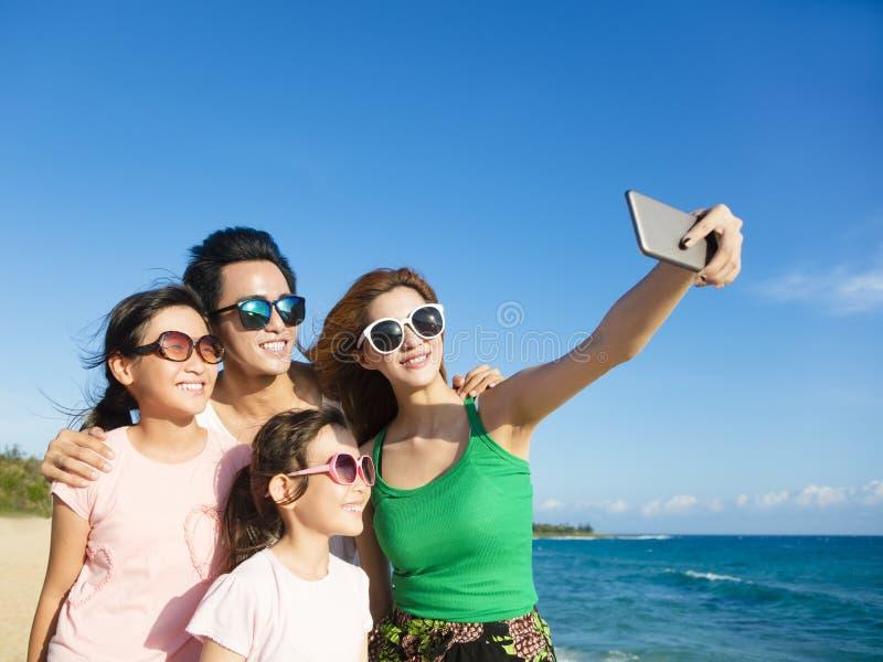 采取selfie的愉快的家庭在海滩 免版税图库摄影