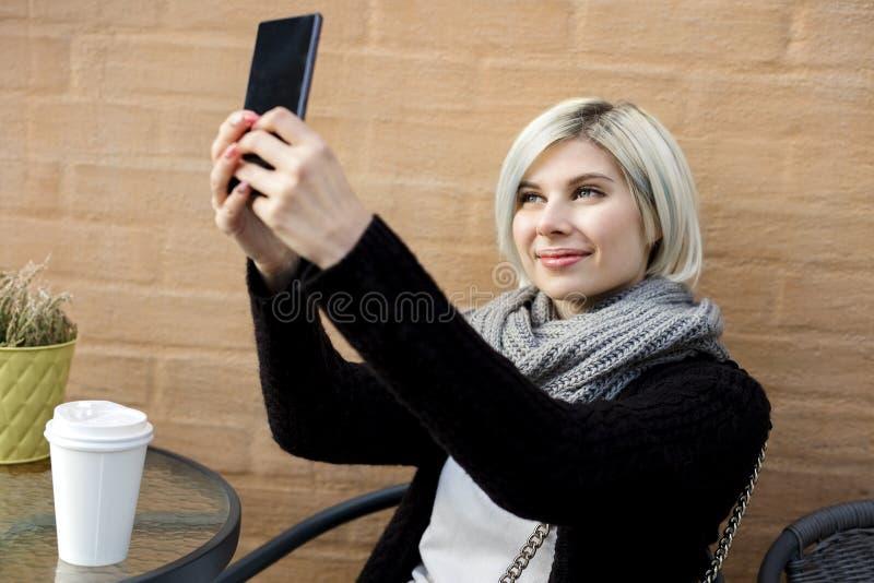 采取Selfie的愉快的少妇在边路咖啡馆 免版税图库摄影