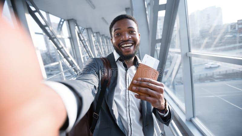 采取Selfie的愉快的蓬松卷发商人在机场,持护照 库存照片