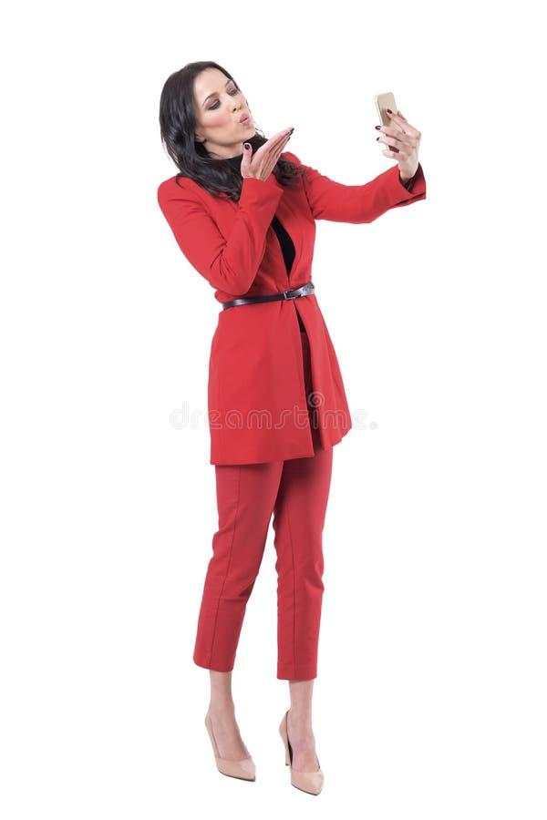 采取selfie的愉快的轻松的女商人送爱和亲吻与照片消息 免版税库存照片