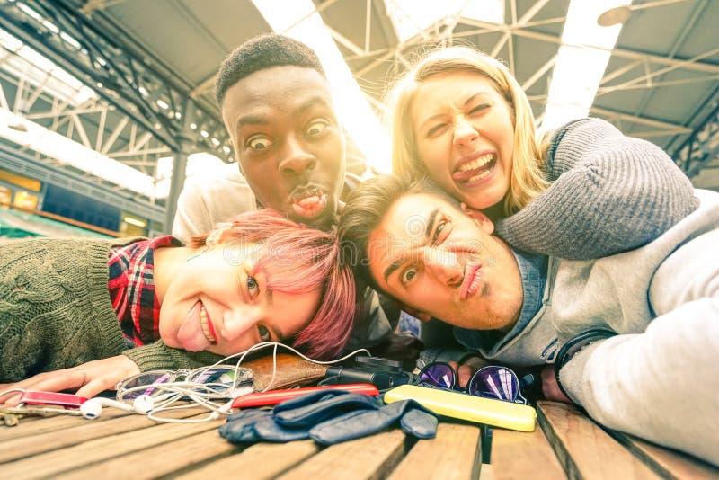 采取selfie的愉快的年轻朋友户内与后面照明设备 免版税库存照片