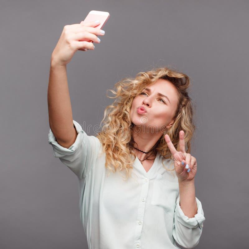 采取selfie的时髦女孩在演播室 库存照片