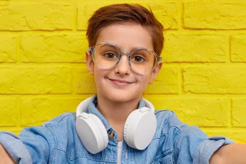 采取selfie的时髦男孩在砖墙附近 库存照片