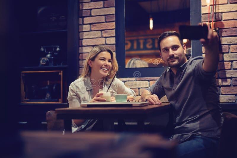 采取selfie的有吸引力的夫妇,当食用一杯咖啡时 - 图象 库存照片