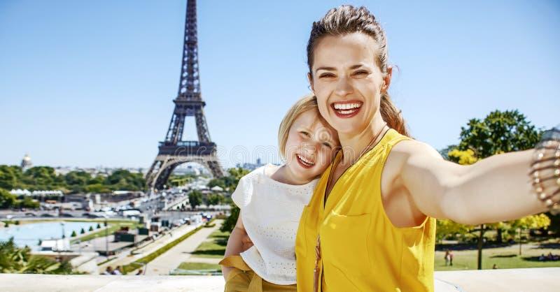 采取selfie的母亲和儿童游人反对埃佛尔铁塔 免版税库存图片