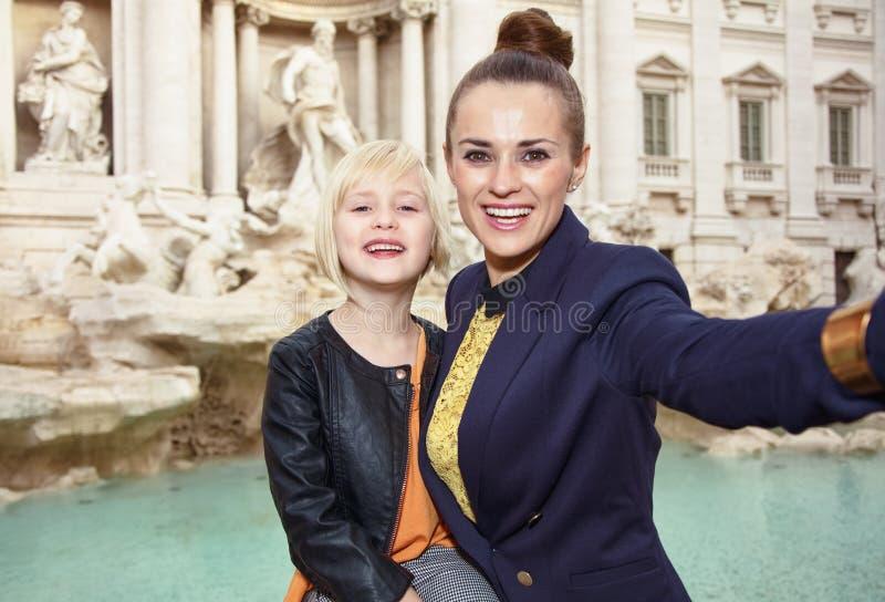 采取selfie的母亲和儿童游人反对Trevi喷泉 免版税库存照片