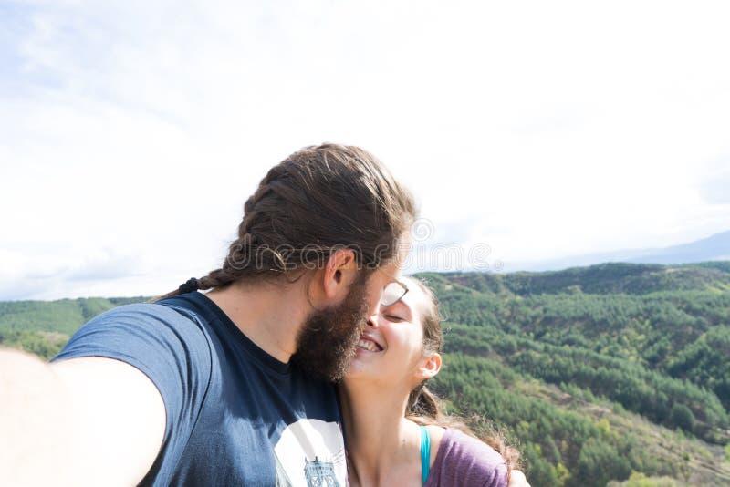采取selfie的爱的夫妇,当亲吻在室外时 有胡子的男朋友 一起旅行的家庭 免版税库存照片