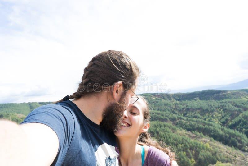 采取selfie的爱的夫妇,当亲吻在室外时 有胡子的男朋友 一起旅行的家庭 库存照片