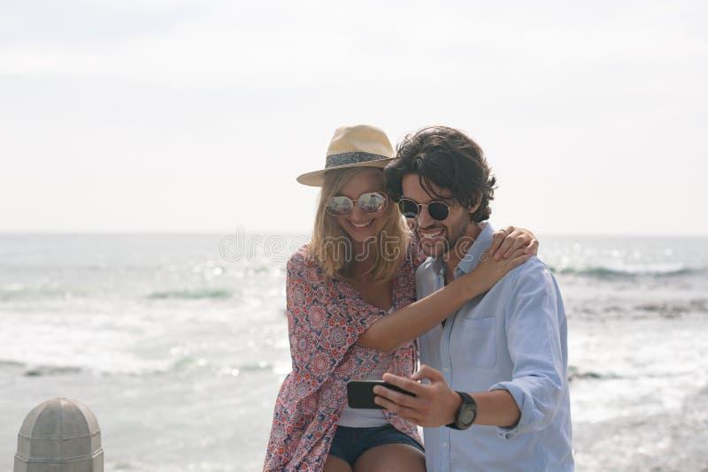 采取selfie的白种人夫妇,当坐靠近海边在散步时 免版税库存照片