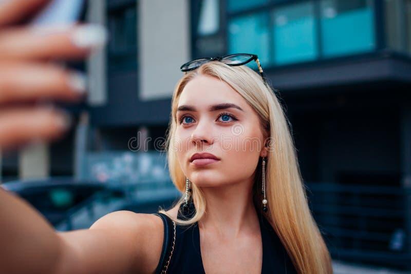 采取selfie的美丽的少妇,当饮用橙汁在室外咖啡馆时 库存照片
