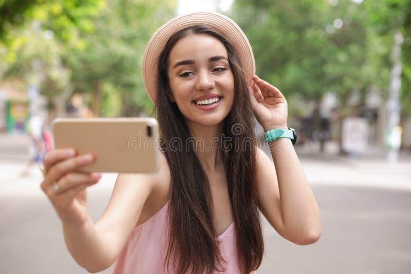 采取selfie的美丽的年轻女人户外 库存照片