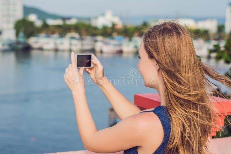 采取selfie的美丽的年轻快乐的妇女以海和越南小船为背景 免版税库存图片