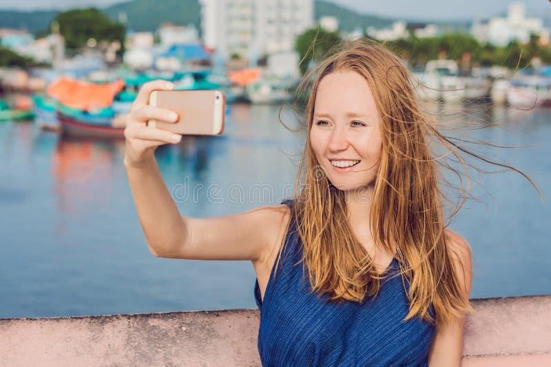 采取selfie的美丽的年轻快乐的妇女以海和越南小船为背景 免版税图库摄影