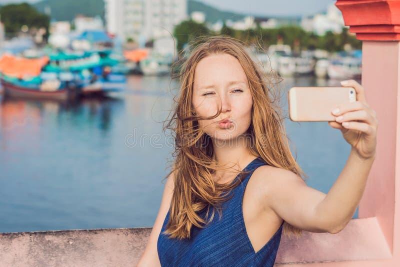 采取selfie的美丽的年轻快乐的妇女以海和越南小船为背景 库存图片