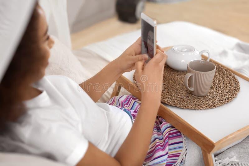 采取selfie的美丽的非裔美国人的妇女,当喝在床上时的茶 库存图片