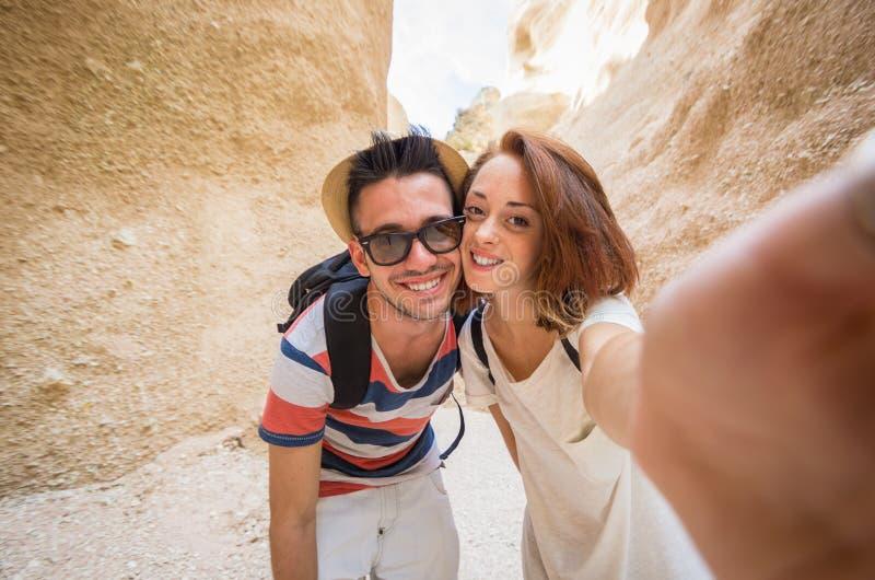 采取selfie的美好的白种人夫妇在大峡谷的一次旅行期间 图库摄影