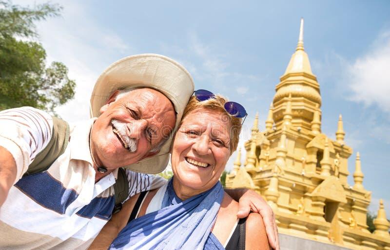 采取selfie的资深夫妇在金黄寺庙在苏梅岛-旅行到泰国奇迹的愉快的退休的人-活跃老人 图库摄影