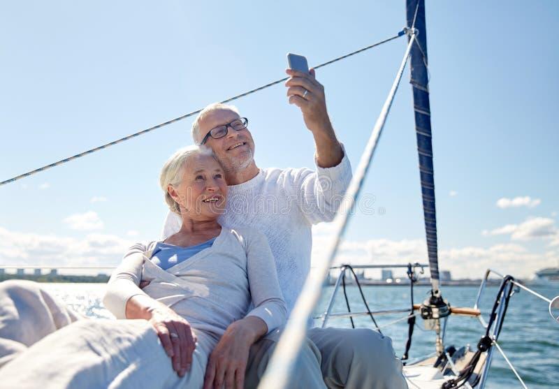采取selfie的资深夫妇由在游艇的智能手机 免版税图库摄影