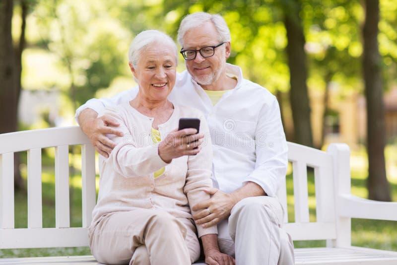 采取selfie的资深夫妇由智能手机在公园 库存照片