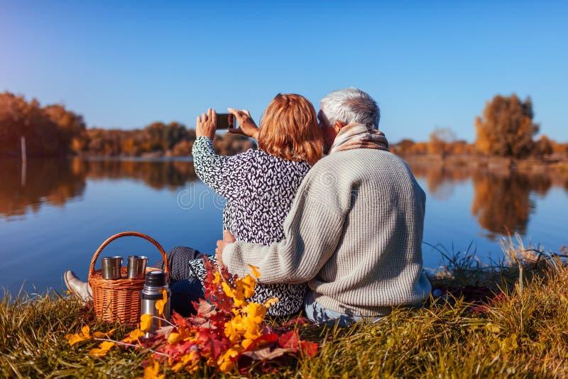 采取selfie的资深夫妇,当有野餐在秋天湖之前时 愉快的享受自然和拥抱的男人和妇女 库存图片