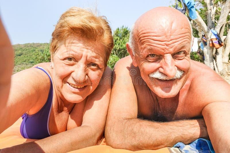 采取selfie的资深愉快的夫妇在泰国旅行的海滩胜地在热带游览中-活跃老人的冒险和乐趣概念 图库摄影